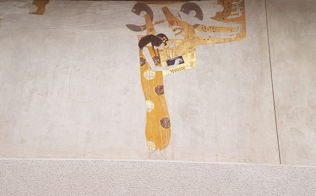 "A fragment of Gustav Klimt's ""Beethoven Frieze"" in the Vienna Secession, the figure of Poetry. Photo: Art with me! e.U., 2019."