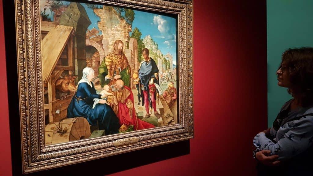 "A viewer in front of Durer's painting ""The Adoration of the Magi"" (1504) at the exhibition in Vienna. Photo: Art with me! e.U., 2019"