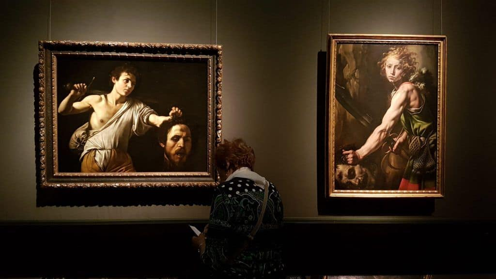 "A viewer in the exhibition ""Caravaggio and Bernini"" at the Museum of Art History in Vienna. Photo Art with me! e.U., 2020"